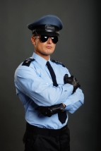 Policeman in uniform with sunglasses on gray background