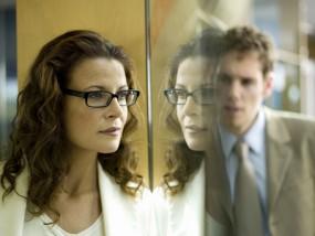 Geschäftsfrau und Geschäftsmann, hinter Fensterscheibe