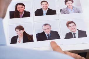 Businessperson Choosing Photograph Of Best Candidate